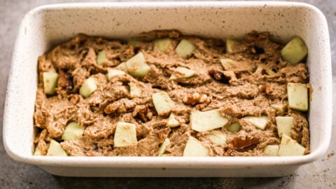 apple bread batter with fresh apples and walnuts spread in a loaf pan