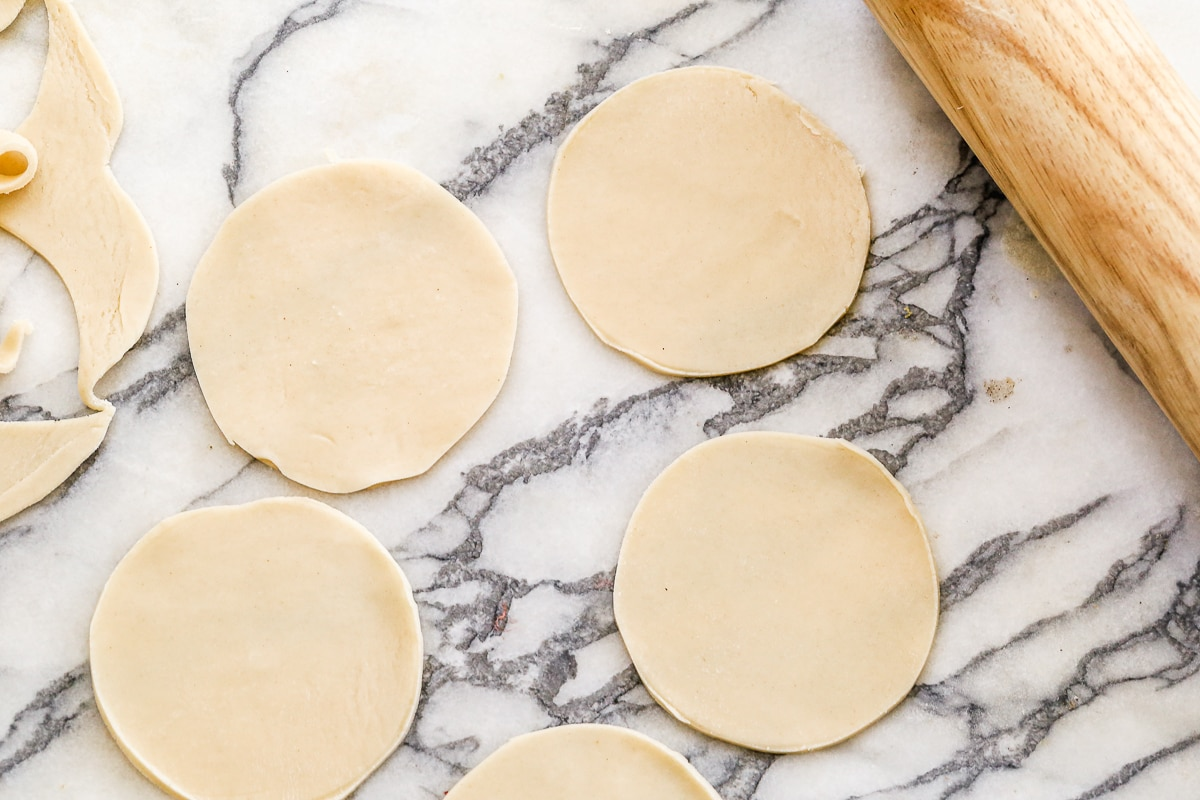 pie crust circles on a marble counter with a rolling pin