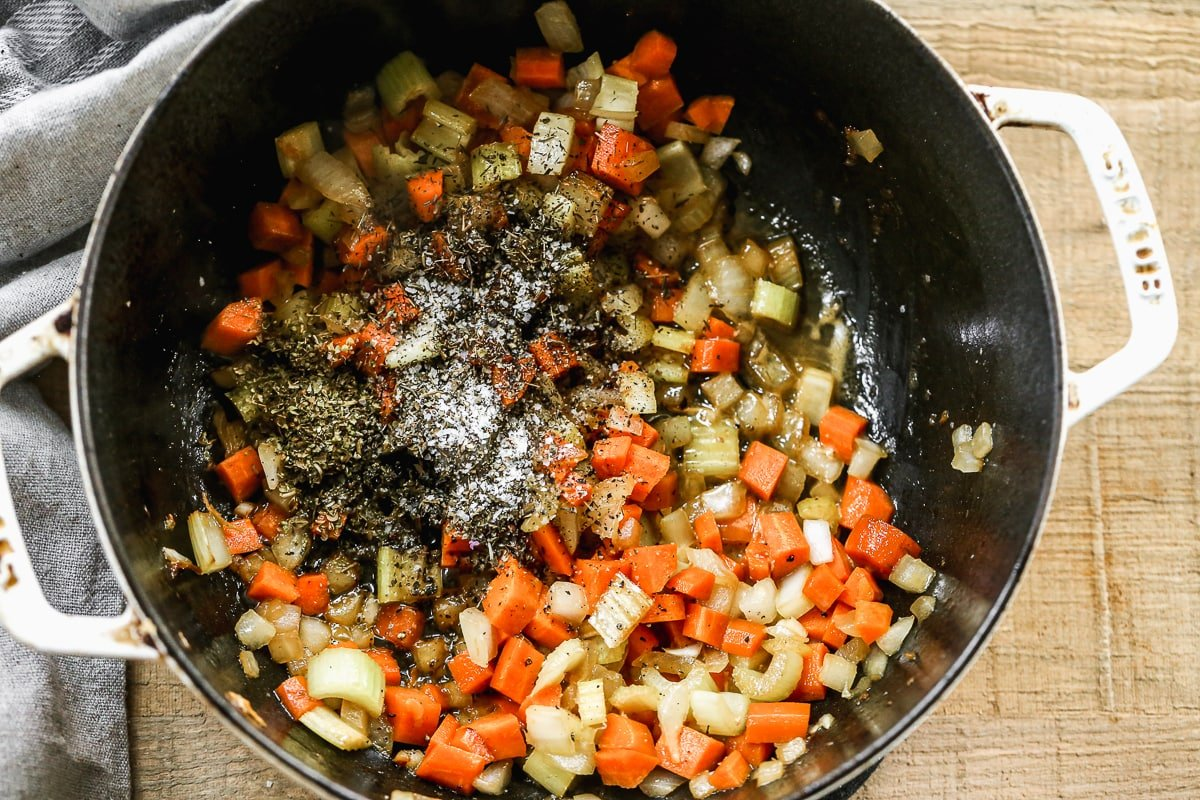 Vegetables being cooked in a pot with spices