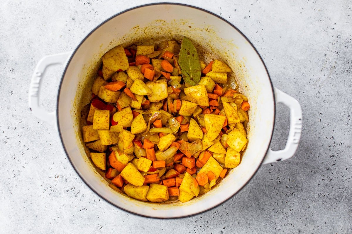 cooking carrots, apples and spices together in a soup pot until tender