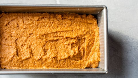 pumpkin bread batter made with whole wheat flour spread into a loaf pan