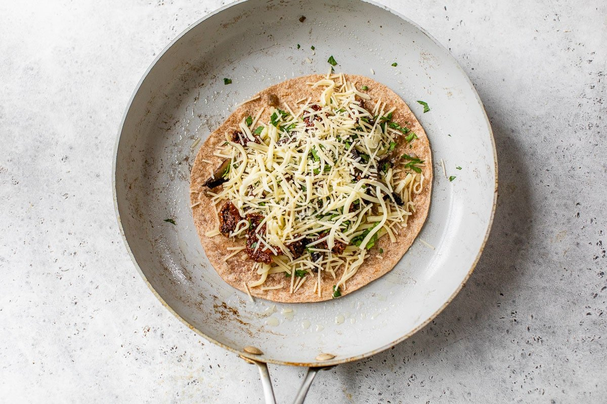 sprinkling cheese, mushrooms, and sun-dried tomatoes on a tortilla in a skillet