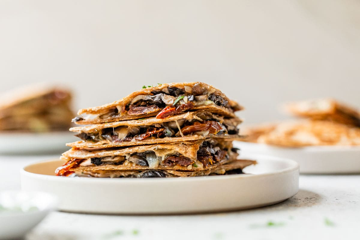 A plate of mushroom quesadilla wedges stacked on a plate