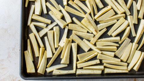 seasoned parsnips cut into fries on a baking sheet