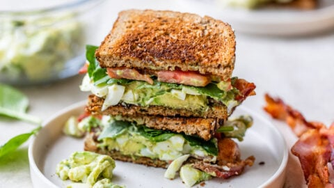 Halves of avocado egg salad sandwich with bacon, tomato and spinach stacked on a plate