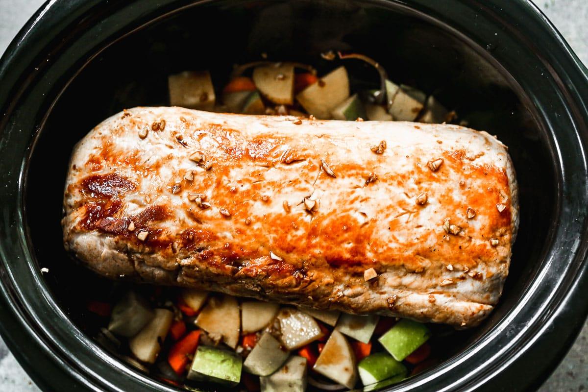 Crock pot pork roast being made with vegetables
